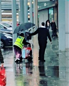 Shoppers clap as Morrisons security guard rushes to help shelter woman from torrential rain
